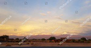O por do sol ilumina-se na paisagem estéril e desolada do deserto de Atacama com os picos dos vulcões nevado da Cordilheira de Andes no fundo. Autor e Copyright Marco Ramerini
